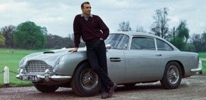 Only James Bond could stand in front of a car like an Aston Martin and completely upstage it.