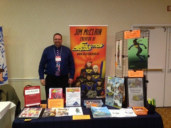 Jim McCain promotes Solution Squad with an organized booth and professional attire.