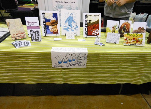 Yeti Press keeps their booth nice and tidy and uses a yellow tablecloth to grab attention.