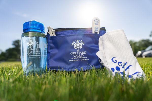 Golf kits filled with water bottles, towels, and golf tees, packaged inside a reusable lunch bag donated to the Fox Valley Park District for their Golf for Kids event