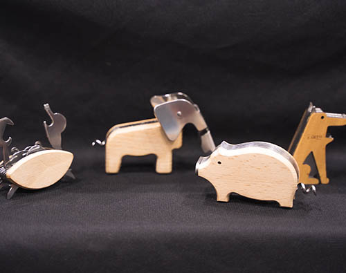 Wood and metal utility knives shaped like animals. From left to right, a crab, an elephant, a pig, and a dog.