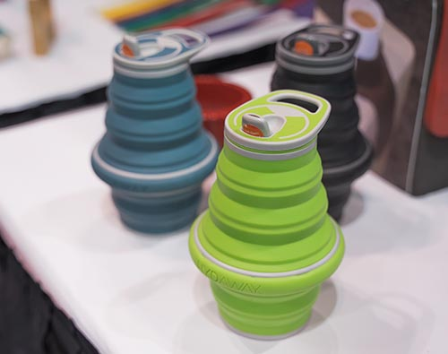 Collapsible silicone water bottles in blue, black, and green. They have many tiers that can be pushed together to compress the water bottle into a flat shape.